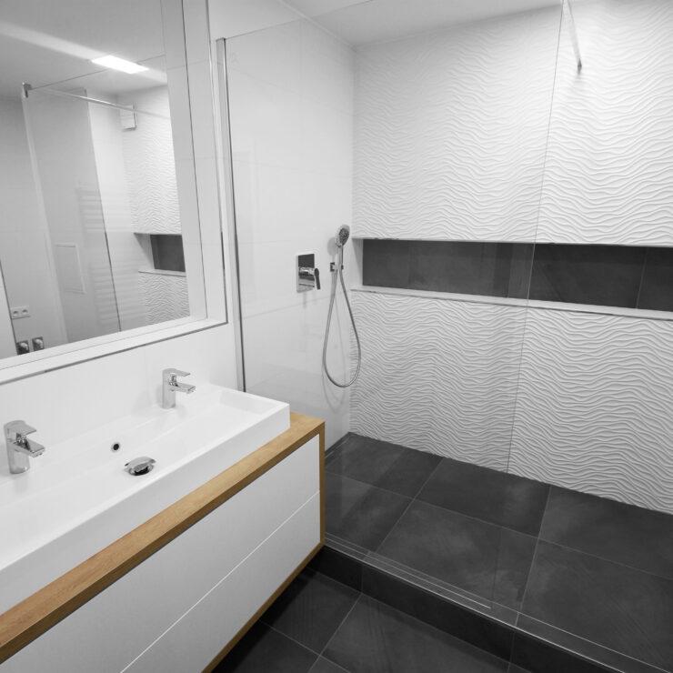 Koupelna s tmavou dlažbou a dřevěnými doplňky